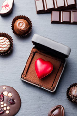 Heart shaped chocolate candy in a gift box on slate background. Top view.