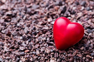 Heart shaped chocolate candy on crushed cocoa nibs. Close up. Copy space.