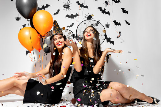 Two brunette women in witches hats smile, have fun with confetti and hold black and orange balloons. Halloween