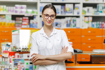 A pretty young girl with dark hair and glasses,wearing a medical overall,stands by the cash desk with her arms crossed  in a up-to-date pharmacy.
