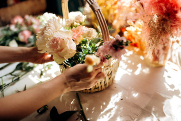 Florist collections a bouquet in the basket from fresh peonies and roses in the flower shop