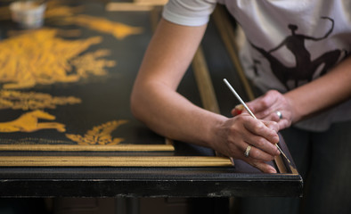 painter decorator draws pattern with a thin brush