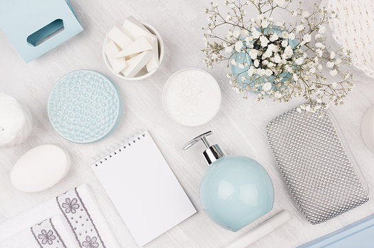 Elegant cosmetics set of accessories for beauty care top view - soap, towel, ceramic pastel blue bowls, silver cosmetic bag, flowers on white wood background.