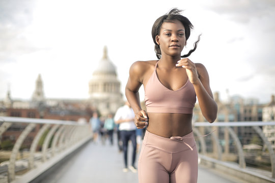 Girl running on Millenniunm Bridge in London