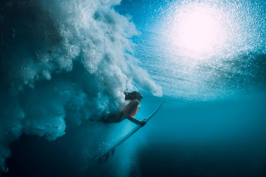Surfer girl with surfboard dive underwater with under big ocean wave.