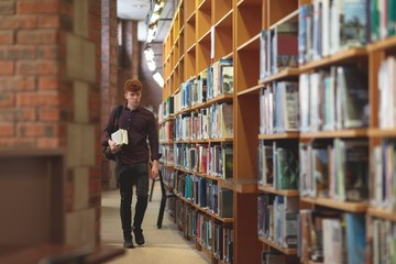 College student with books walking in library