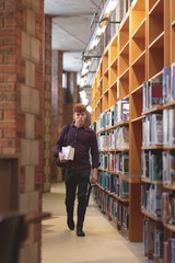 College student with a books walking in library