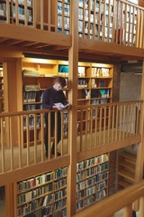 College student reading a book in library