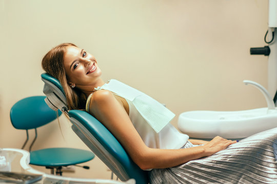 Happy pretty female patient in dental office.