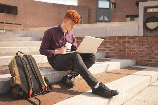 College student using laptop on stairs