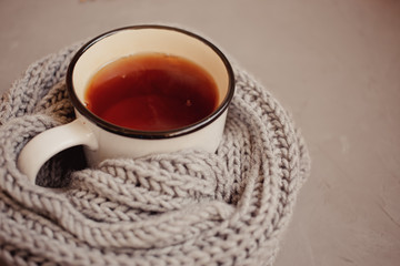 warm scarf, cup of tea on gray background, top view, with copy space