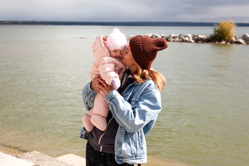 Atmospheric lifestyle photo of woman in a denim jacket  walks and plays with his little  daughter baby  against the background of sea in sunny day.