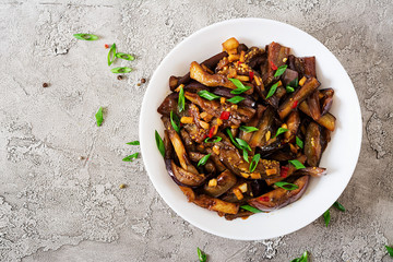 Hot spicy stew eggplant in Korean style with green onion. Aubergine saute. Vegan food. Flat lay. Top view