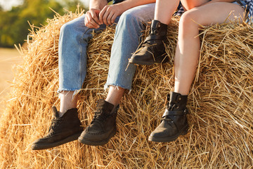 Cropped photo of stylish man and woman sitting on big haystack in golden field, during sunny day
