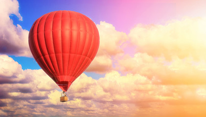 Red balloon against a blue cloudy sky. Sun rays and glare. Dreamy clouds. Aerostat. People in the basket. Fun. Summer entertainment. Romantic adventures.