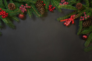 Christmas holiday background - tree, gifts, holly berries and decoration on black chackboard. Holiday card with copy space. Top view.