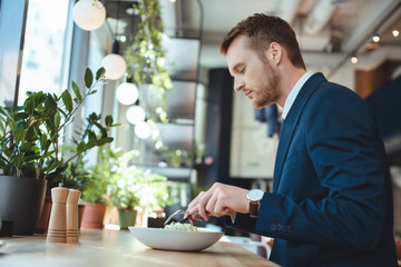 side view of businessman in suit having lunch in cafe