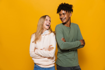 Photo of teenage people man and woman 16-18 with dental braces smiling, isolated over yellow background