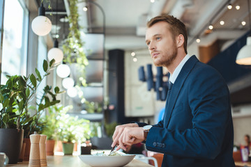 side view of thoughtful businessman looking away while having lunch in cafe