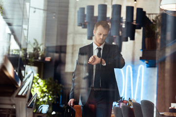 businessman in fashionable suit with suitcase checking time while walking in cafe
