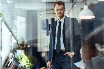 portrait of smiling businessman in stylish suit with hand in pocket standing in cafe