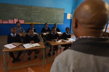 Male teacher teaching students in the classroom
