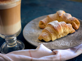 A cup of fresh coffee with croissants on a dark blue background, selective focus