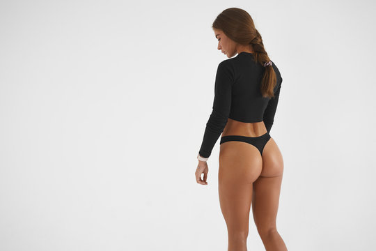 Back view of sensual brunette woman wearing black top and thongs, demonstrating perfect strong butt muscles at camera. People, active lifestyle, beauty, sports, fitness and determination concept