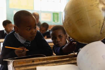 Schoolkids looking at globe in classroom