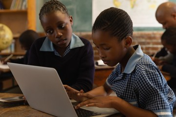 Schoolkids using laptop in classroom