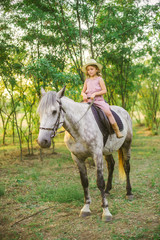 Little cute girl with light curly hair in a straw hat riding a horse at sunset on a sunny warm autumn day