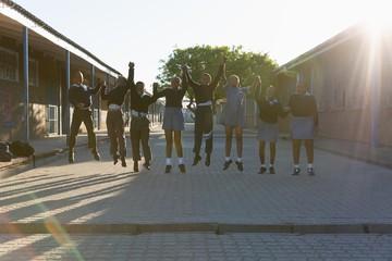 Schoolkids holding hands in school campus