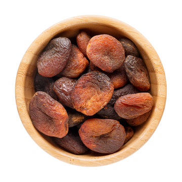 Dried apricots in wooden bowl isolated on white. Top view