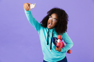 African girl posing isolated over violet background holding skateboard take a selfie by phone.