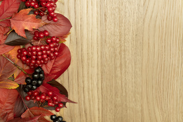 Autumn red leaves frame on oak wooden background
