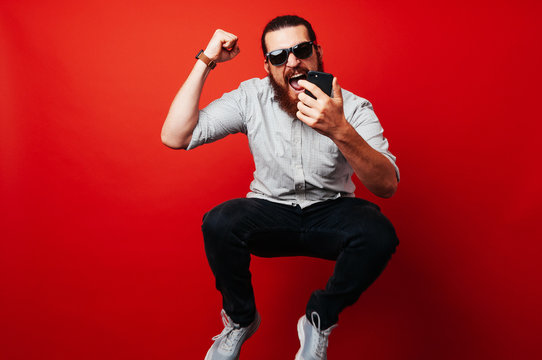 Photo of excited bearded man jumping isolated over red background wall using mobile phone