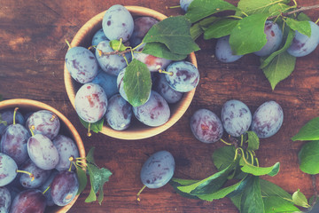 Fresh plums on wooden table. Toned.