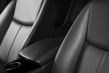 Modern luxury car black leather interior. Part of leather car seat with stitching. Interior of prestige modern car. Comfortable perforated leather seats. Black perforated leather. Car detailing