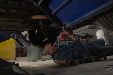 Male mechanic servicing a car