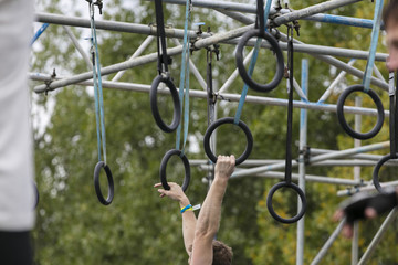 A person on hanging rings during an adventure obstacle course race