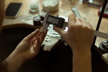 Jewelry designer using caliper in workshop