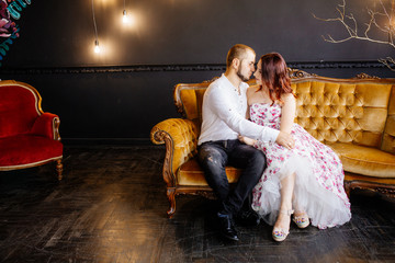 Wedding couple have a photo session in the amazing studio. Young couple hug and kiss while sitting at old sofa. Man and woman at family photo session. Young married couple.