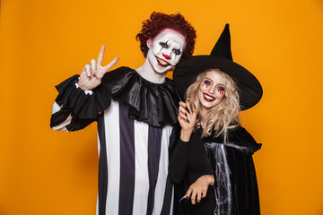 Smiling woman witch and clown looking camera and smiling isolated