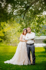 Bride and groom in a park kissing. Young wedding couple newlyweds bride and groom at a wedding in nature green park near lake. Walking and kissing photo portrait. Before wedding ceremony.