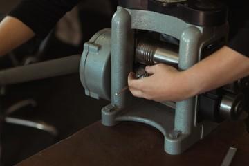 Jewelry designer using a machine in workshop