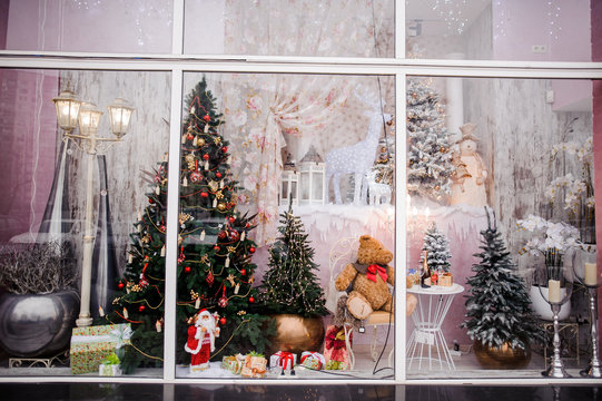 Beautiful festive Christmas storefront with decorated artificial Christmas trees and toys