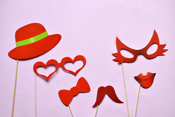 Colorful props for party. Carnival accessories set. Paper glasses, hat, lips, moustaches, tie on wooden sticks.