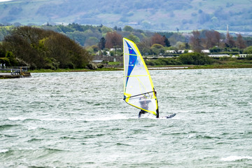 Man windsurfing close to the town of Caernarfon in Wales - United Kingdom