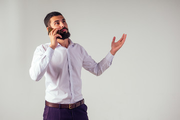Businessman barber shop owner using mobile phone . Young caucasian bearded man holding smartphone for business work.