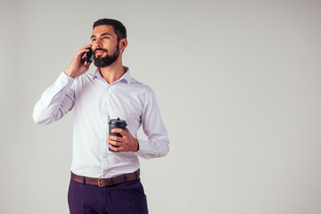 handsome Arab Sheikh businessman black beard in a white shirt and black trousers holding a plastic paper cup and drinking coffee , using a smartphone on white background studio shot